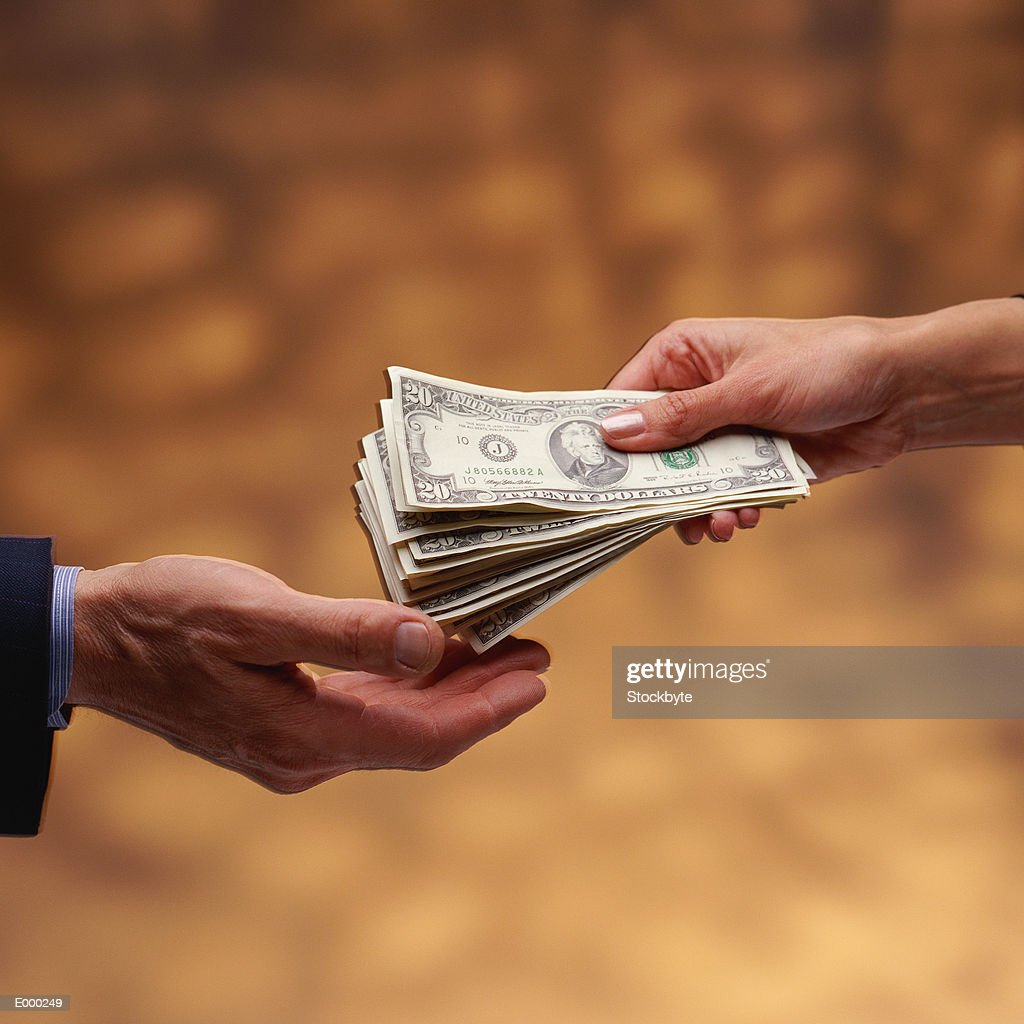 Woman's hand giving stack of US $20 bills to man's hand : Stock Photo