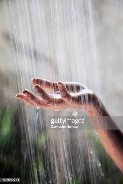 Woman's hand held under shower water