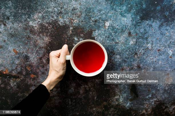 a woman's hand holding a cup of hot and red herbal tea - circle stock pictures, royalty-free photos & images