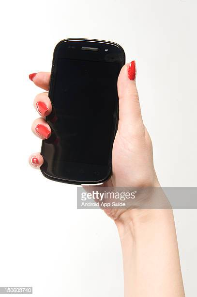 A woman's hand holding a Google Nexus S smartphone during a studio shoot for Android App Guide February 11 2011