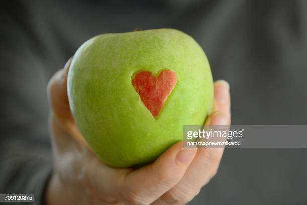 Woman's hand holding a Green apple with red heart