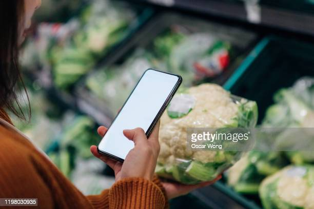 woman's hand holding a mobile phone with blank screen to scan product code in grocery store - merchandise stock pictures, royalty-free photos & images