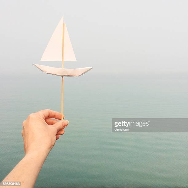 Woman's hand holding a paper boat by ocean