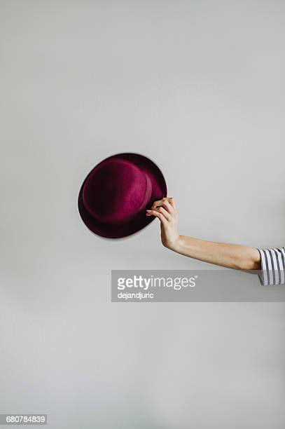 Woman's hand holding a red hat