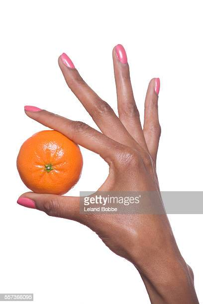 Woman's hand holding a tangerine
