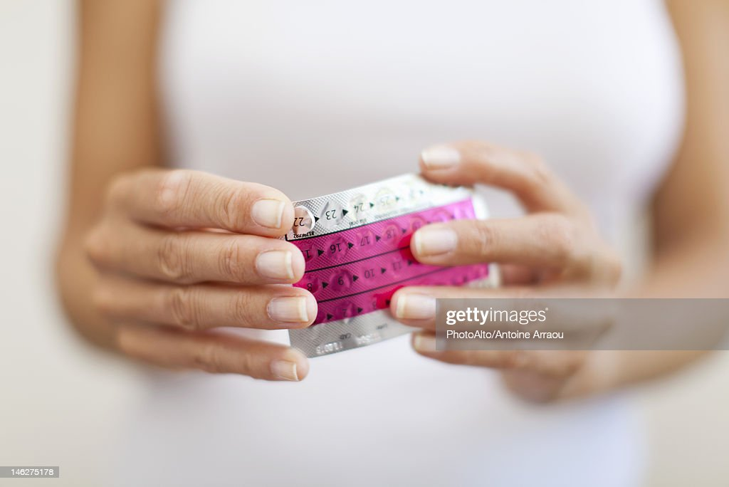 Woman's hand holding birth control pills, cropped : Stock Photo