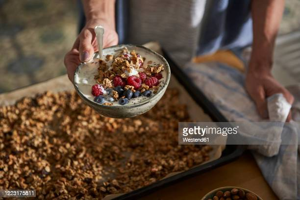 woman's hand holding bowl of granola with yoghurt and berries - 調理方法 ストックフォトと画像