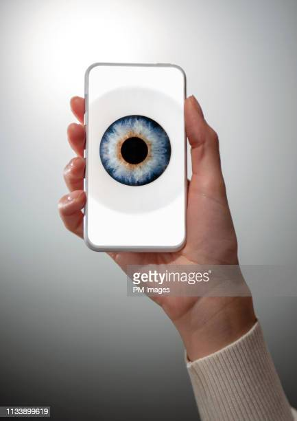 woman's hand holding cell phone with eye on screen - big brother orwellian concept stock pictures, royalty-free photos & images