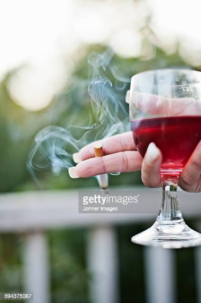 Womans hand holding cigarette and glass of wine