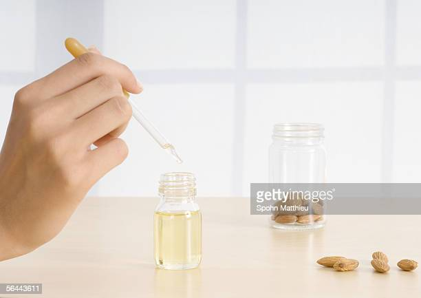 Woman's hand holding dropper of essential oil with almonds