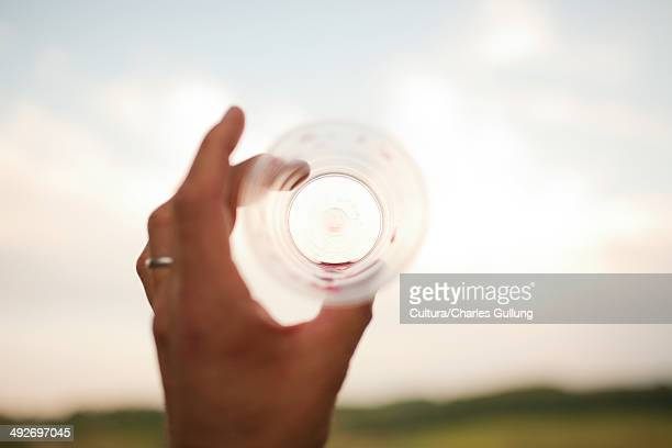 Woman's hand holding empty drinking glass