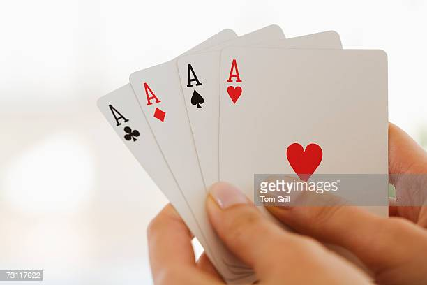 Womans hand holding four aces