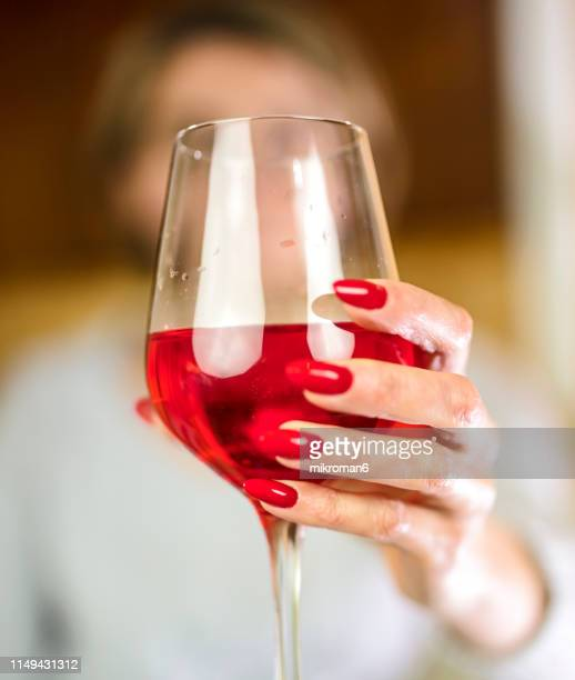 woman's hand holding glass of red wine. alcohol addiction - drunk stock pictures, royalty-free photos & images