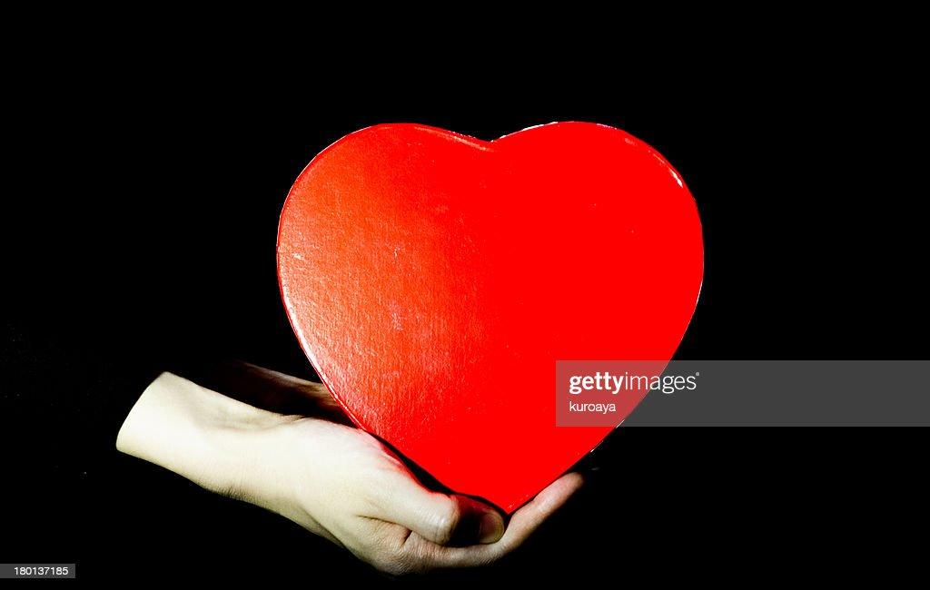 Woman's hand holding heart-shaped box : Stock Photo