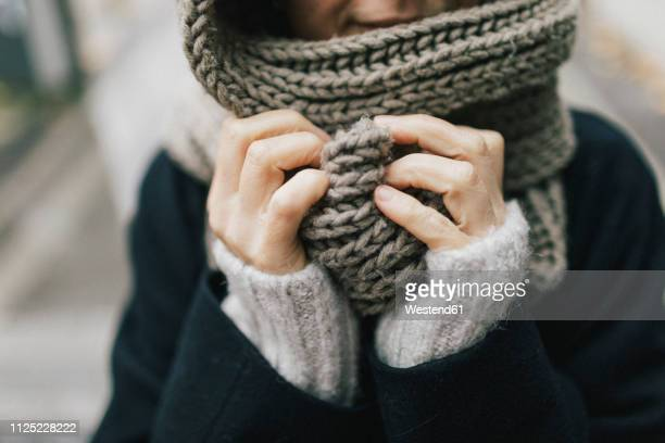 woman's hand holding knitted scarf, close-up - kälte stock-fotos und bilder