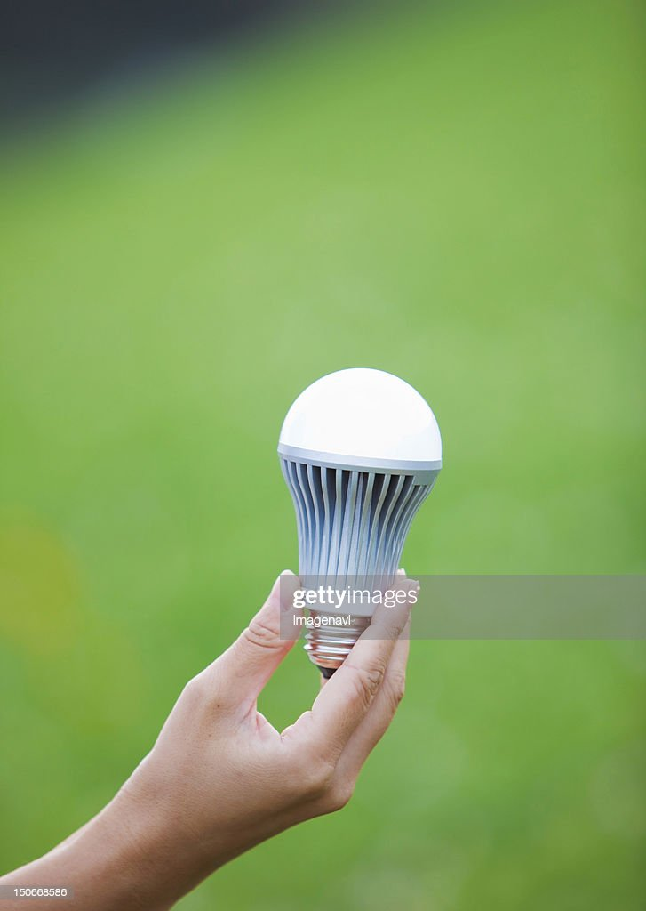 Woman's hand holding LED bulb : Stock Photo