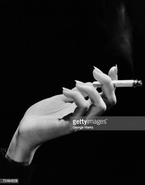Woman's hand holding lit cigarette