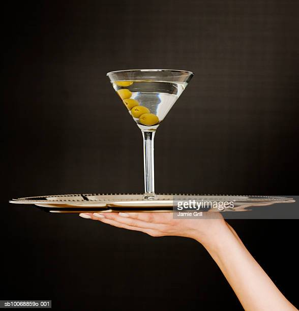 Woman's hand holding martini on tray, close-up