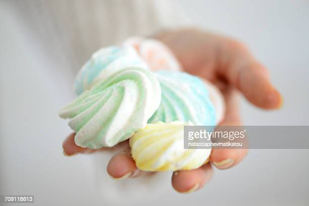 woman's hand holding, meringues - meringue stock pictures, royalty-free photos & images