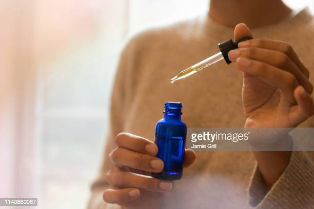 woman's hand holding pipette and bottle of aromatherapy oil - pipette stock pictures, royalty-free photos & images
