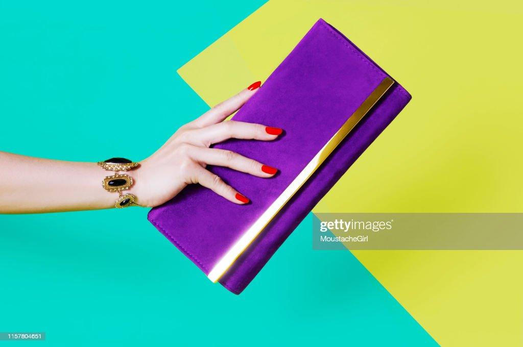 Woman's hand holding purple purse : Stock Photo