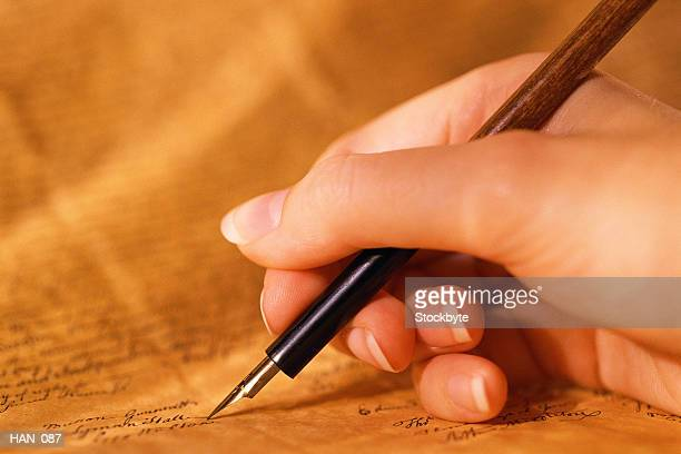 Woman's hand holding quill pen, writing on parchment paper