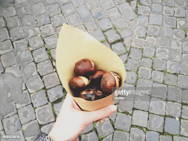 womans hand holding roasted chestnuts wrapped in paper - chestnut food stock pictures, royalty-free photos & images