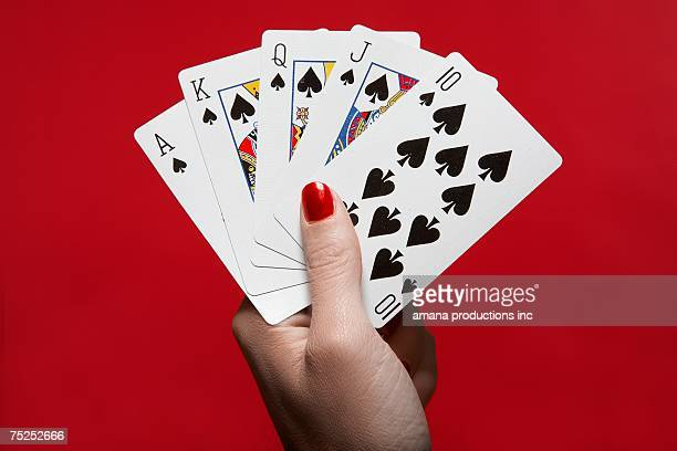 woman's hand holding 'royal flush' hand of cards - hand of cards stock photos and pictures