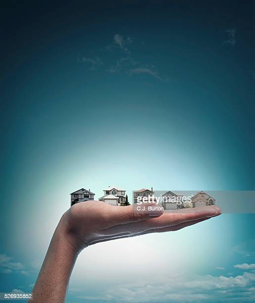 Woman's Hand Holding Several Houses