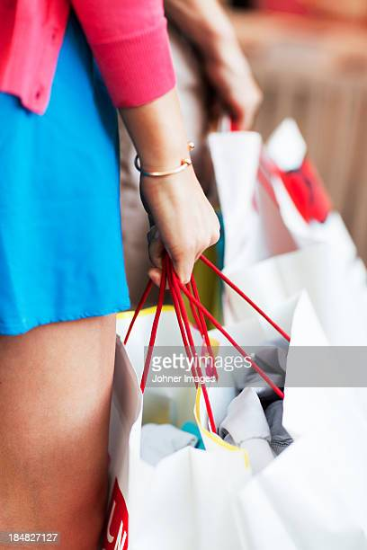 Womans hand holding shopping bags
