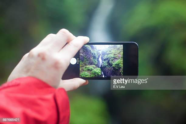 Womans hand holding smartphone, photographing Aira Force waterfall, Penrith, Cumbria, UK