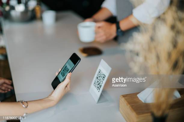 woman's hand holding smartphone, scanning barcode for contactless payment in the cafe - finance and economy stock pictures, royalty-free photos & images