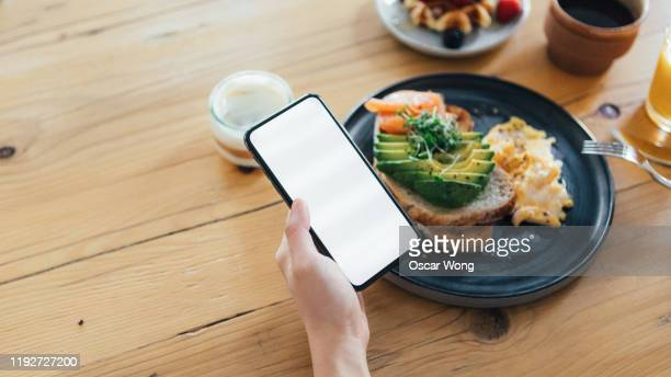 woman's hand holding smartphone while having brunch, personal perspective - day stock pictures, royalty-free photos & images