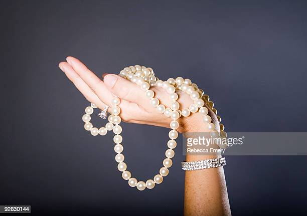 woman's hand holding string of pearls - halskette stock-fotos und bilder