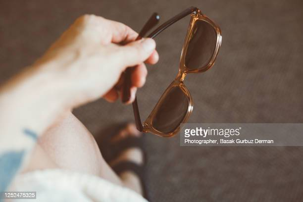a woman's hand holding sunglasses - fashion week stock pictures, royalty-free photos & images