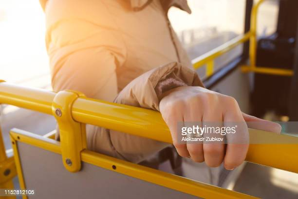 woman's hand holding the handrail in the bus. a young girl, a passenger in public transport. the concept of urban life. close up. - veiligheidshek stockfoto's en -beelden