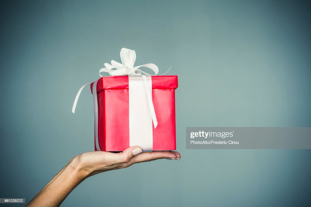 Womans hand holding wrapped gift : Stock Photo
