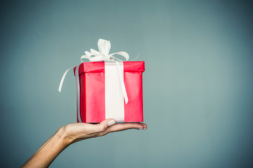 Womans hand holding wrapped gift - gettyimageskorea