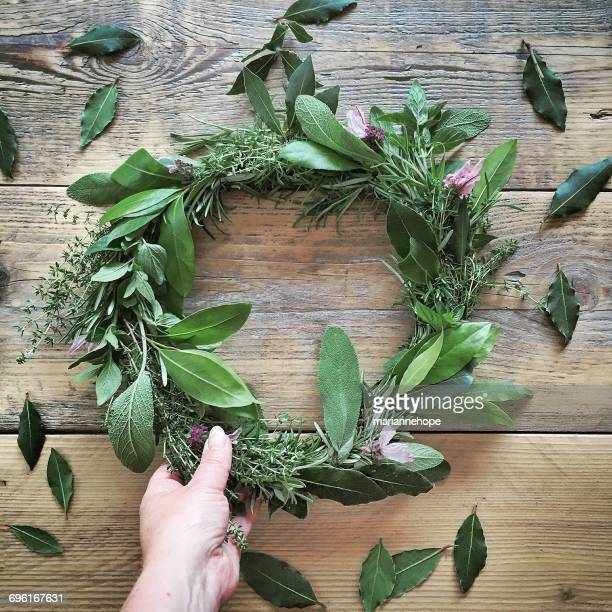 Woman's hand holding wreath of herbs