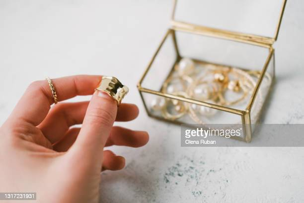 a woman's hand holds a gold ring - jewellery stock pictures, royalty-free photos & images