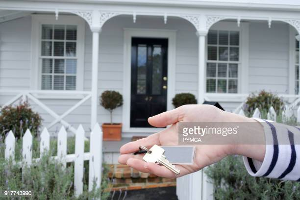 A womans hand holds a key against a front of a traditional villa house in Auckland New Zealand Buy sale real estate insurance mortgage bank loans and...