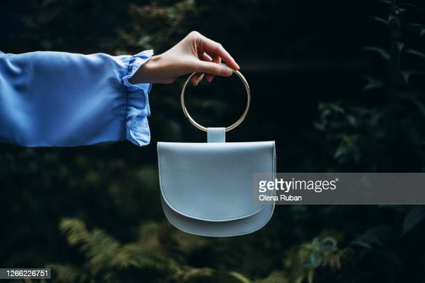 a woman's hand holds handbag in her hand on a dark background - design stock pictures, royalty-free photos & images