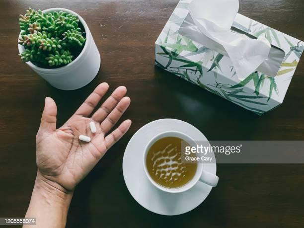 woman's hand holds pills above wood table - immunsystem bildbanksfoton och bilder
