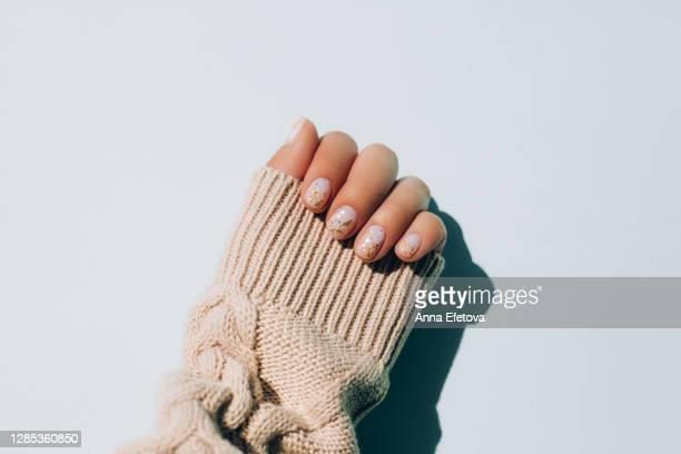 woman's hand in warm sweater showing manicure - fragilità foto e immagini stock