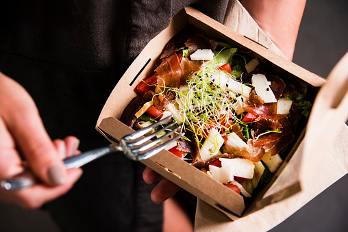 Woman's hand is holding a take away fresh salad in a lunch box. 1044224574