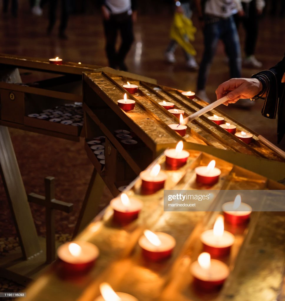 Woman's hand lighting candles in church. : Stock Photo