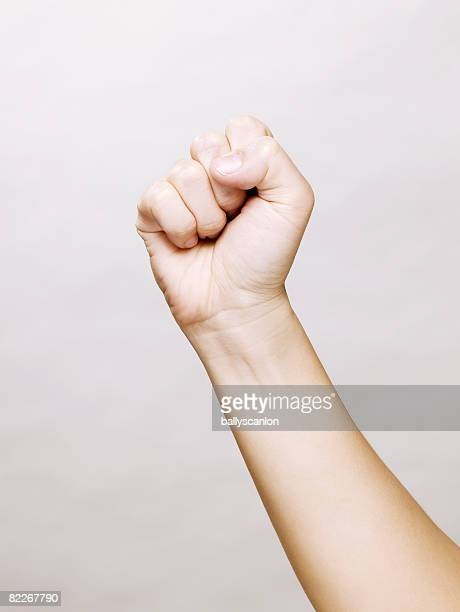 woman's hand making a clinched fist - fist stock pictures, royalty-free photos & images