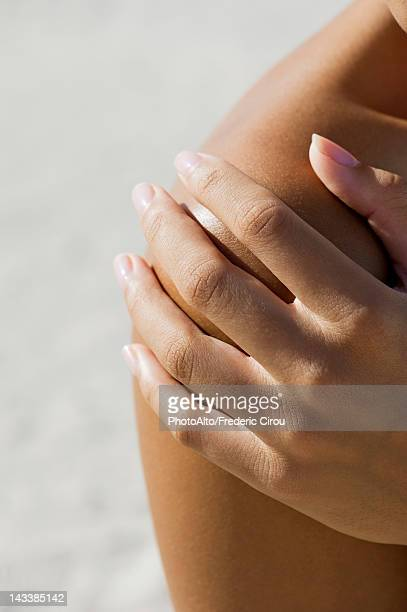 Woman's hand on bare shoulder, cropped
