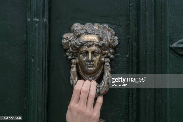 woman's hand on door knocker, close-up - knocking on door stock photos and pictures