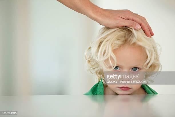 woman's hand on her daughter's head - femme bouder photos et images de collection
